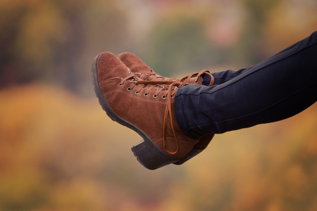 Female foots in brown shoes on a blurred autumn background. Close-up