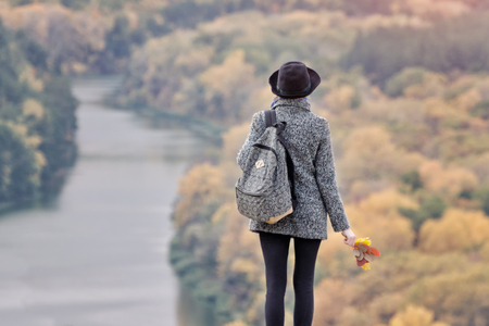 Girl with a backpack and a hat standing on a hill. River and forest below. Back view Stock Photo
