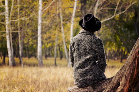 Girl in a hat sitting on a log in the autumn forest. Back view.