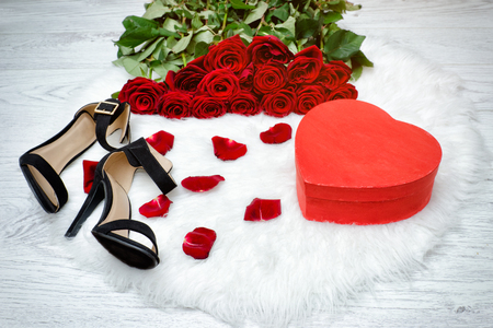 Red boxes in heart shape, black shoes and a bouquet of red roses on a white fur Stock Photo