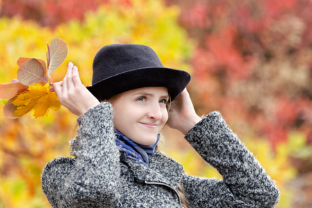 Girl in a hat with a bouquet of yellow leaves. Autumn forest.