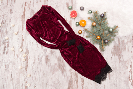 Evening velvet burgundy dress. Halves of citrus and fir branch. Fashionable concept.