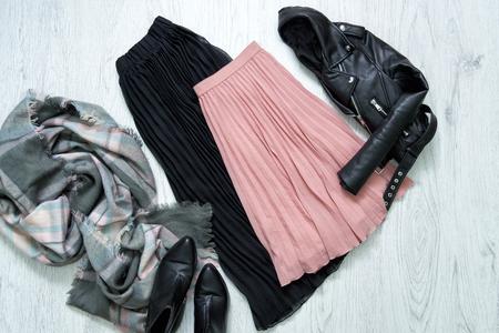 Zwarte en roze rok, jas, sjaal en laarzen. Modieus concept
