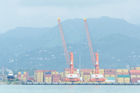 shipbuilding: BATUMI, GEORGIA - 8 JULY 2017: Large port cranes and containers. Mountains in the background