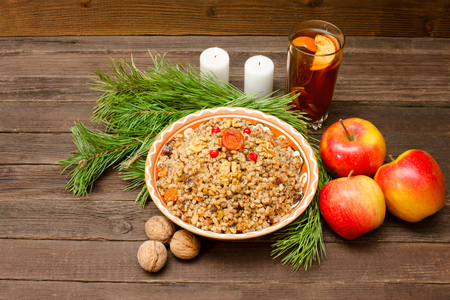 Dish of traditional Slavic treat on Christmas Eve. Pine branches, candles, apples, walnuts, glass of compote. Brown wooden background. 版權商用圖片