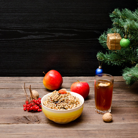 Dish of traditional Slavic treat on Christmas Eve. Christmas tree, apples, walnuts, glass of compote, viburnum. Brown and blak wooden background. Copy space