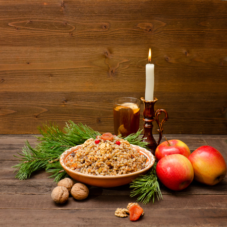 Dish of traditional Slavic treat on Christmas Eve. Pine branches, candles, apples, walnuts, glass of compote. Brown wooden background. Stock Photo