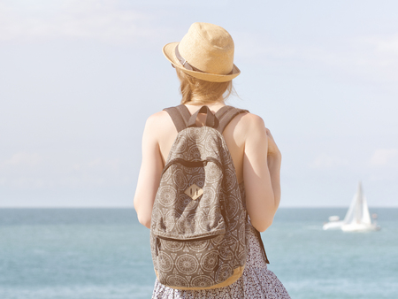Girl in a hat with a backpack standing on the coastline. Sailboat in the distance. Back view Stock Photo