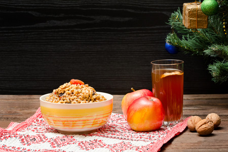 Dish of traditional Slavic treat on Christmas Eve. Christmas tree, apples, walnuts, glass of compote on a patterned tablecloth. Brown and blak wooden background.