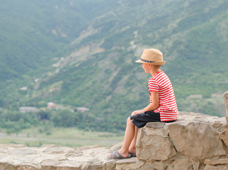 Boy in a hat sitting on stones on a background of green mountains