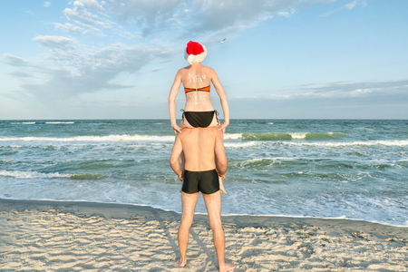 Girl in Santa hat sits on the shoulders of a guy. Sea shore. Back view