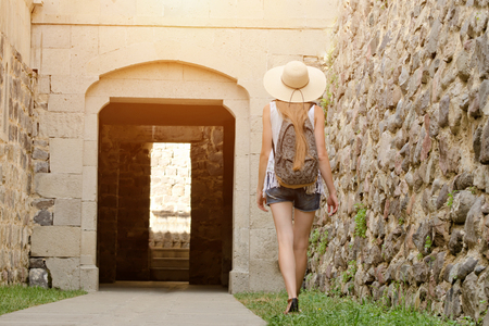 Girl in a hat and with a backpack walking along the fortress, sunlight. Back view Stock Photo