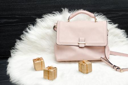 Pink bag and gift box on white fur, black table. Fashionable concept