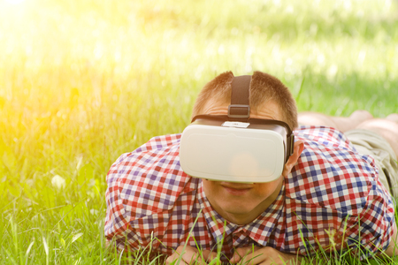 Man in a helmet of virtual reality lies on a green grass