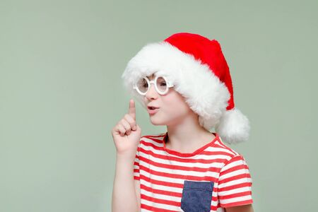 Boy in santa hat and glasses threatens finger