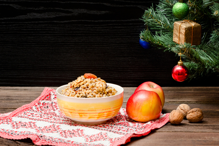 Dish of traditional Slavic treat on Christmas Eve. Christmas tree, apples, walnuts on a patterned tablecloth. Brown and blak wooden background.