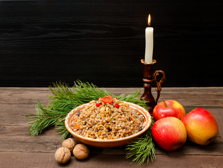Dish of traditional Slavic treat on Christmas Eve.  Pine branches, candles, apples, walnuts. Brown and blak wooden background. Copy space