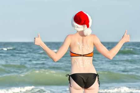 Girl in Santa hats with the inscription New Year on the back on the beach. Thumbs up