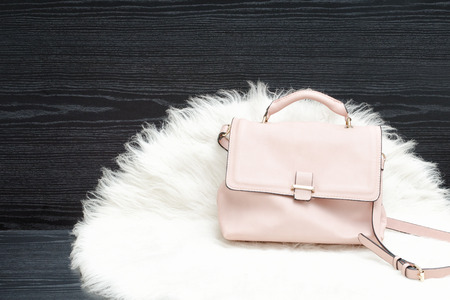 Pink bag on white fur, black table. Fashionable concept