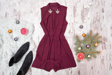 Burgundy dress, shoes and spruce branch on a wooden background. Fashionable concept.