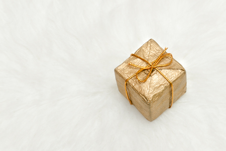 Golden gift box on a white background, copy space. Holiday concept