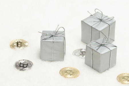 Silvery gift boxes and bitcoins coins on a white background