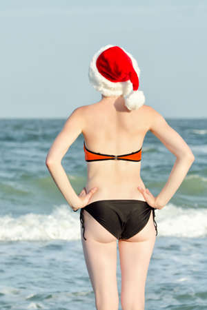 Girl in hat of Santa on the seashore. Back view