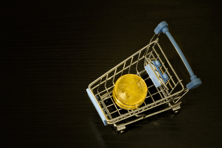 Bitcoin coins in shopping cart. Black background Stock Photo