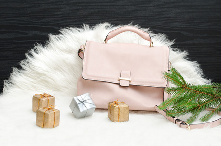 Pink bag, gift boxes and spruce branch on white fur. Fashionable concept