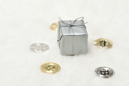 Silvery gift box and bitcoins coins on a white background Stock Photo