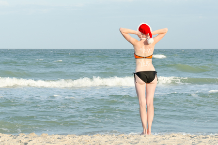 Girl on the sea shore with an inscription on the back and santa hat looks into the distance