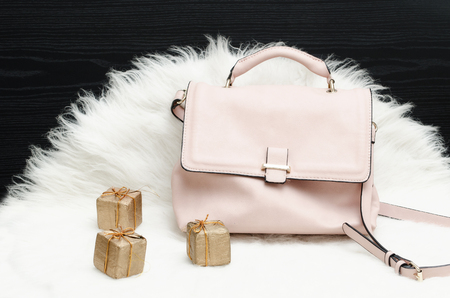 Pink bag and gift box on white fur, black table. Fashionable concept