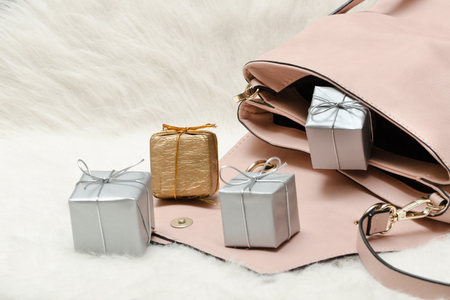 Pink handbag with small gift boxes. Holiday concept Stock Photo
