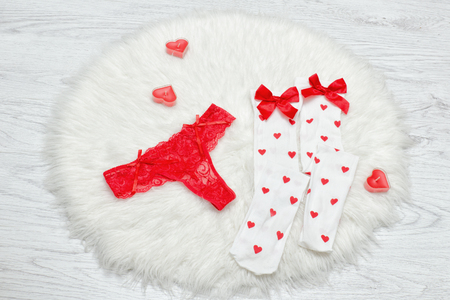 Fashion concept. Red thong panties and white stockings with bows, candles in the shape of a heart on a white fur.