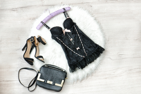 Fashionable concept. Black lacy underwear, handbag and shoes on the white fur.