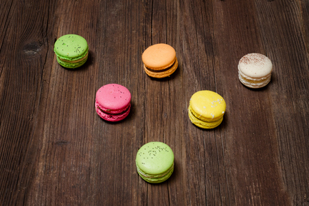 Six multicolored macarons on a brown wooden table. Top view Stock Photo