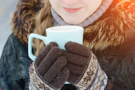 Girl in the brown gloves holding a blue mug of tea, part of the face, close-up