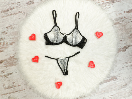 Fashionable concept. Sexy lacy underwear and red candles on the white fur. Flat lay