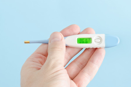 Electronic thermometer in a man's hand. Close-up Stock Photo