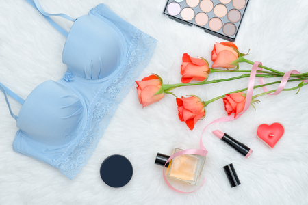 Blue bodice with lace on white fur, orange roses. Lipstick, parfums and candle.  Fashionable concept.  Stock Photo