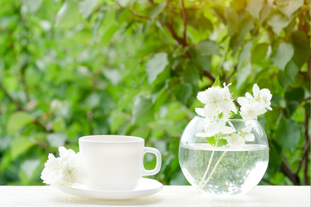 White mug of tea and a vase with jasmine. Greens on the background