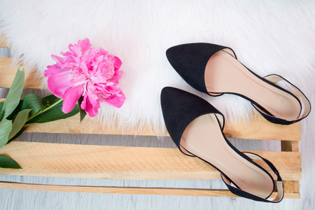 Black shoes on white fur. Bouquet of peonies. Fashionable concept 免版税图像