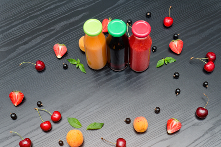 Three bottles of juice and fruits. Black wooden background. Copy space