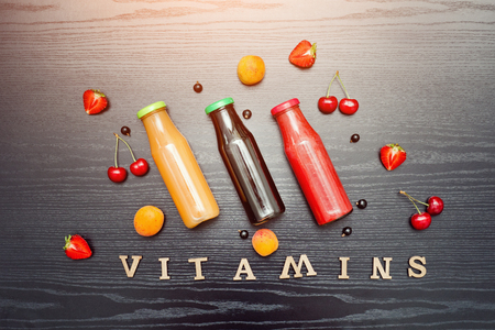 Fruits, juice in bottle and inscription vitamins on a black wooden background. Food concept