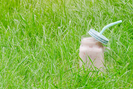 Mug of yogurt on a background of green grass. Space for text Stockfoto