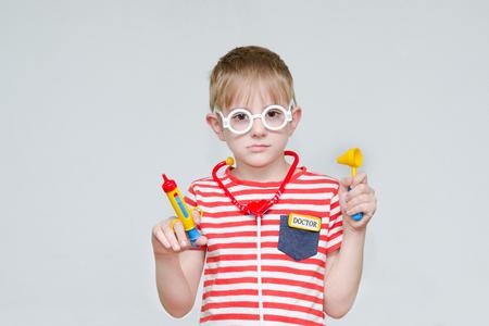 Pensive boy playing doctor. Toy syringe, glasses and phonendoscope. Portrait