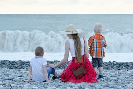 Mom and two sons sitting on the beach and watching the waves. Back view Stock Photo