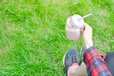Strawberry smoothies in female hand on a background of green grass