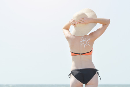 Girl in a hat against the sky. Picture of the sun on the back
