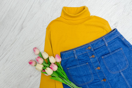 Fashion concept. Yellow turtleneck, blue skirt and pink tulips. Wood background